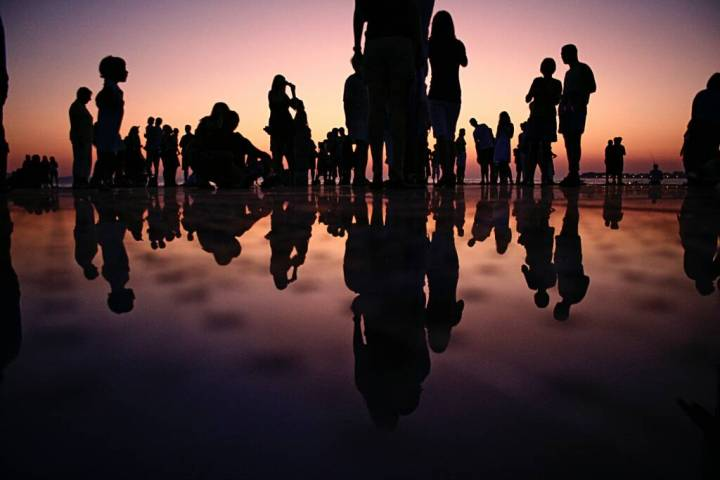 Photograph of a silhouette of a group of people standing in shallow water with sky and silhouettes reflected in water.