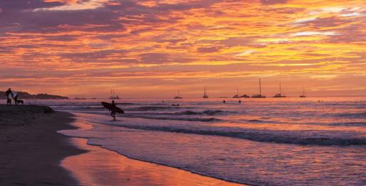 A surfer comes out of the water during a magnificient sunset.