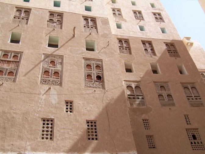 The distinct architecture of the 500 year-old skyscrapers is shown in a wall with beautiful wooden shuttered windows