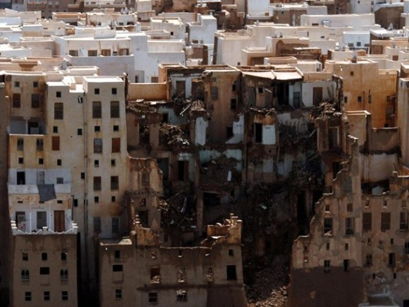 An aerial picture of the side of one of the 500-year-old skyscrapers that was ruined by the flood in 2008. It is black, collapsing, it looks like it's rotting