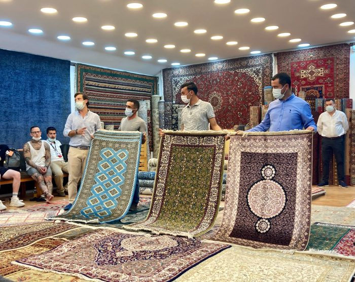 Three men holding up three different types of Turkish rugs in a sales pitch, with another man explaining. Carpets cover the floor and walls of the room.