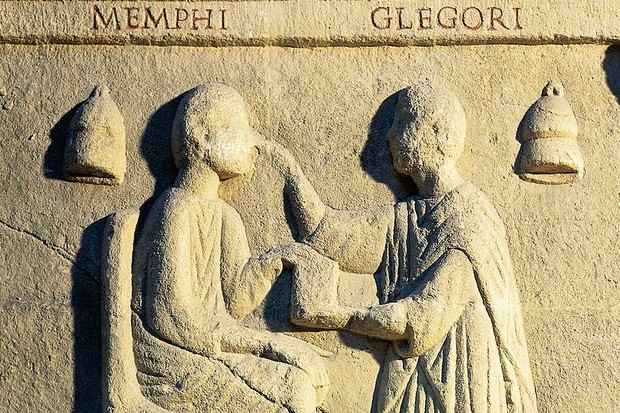 A carving out of stone showing a roman doctor giving a remedy to a seated patient