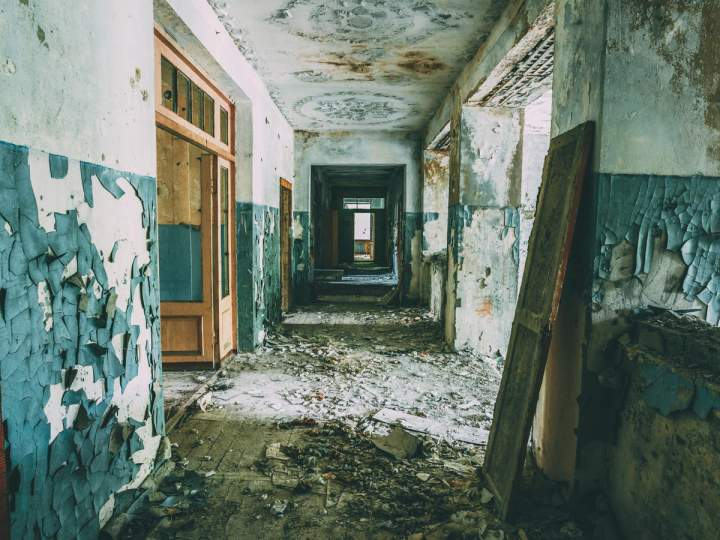 A blue and white paint stripped hall with door frames leaning against the walls and rubble strewn across the floor. dark tourism