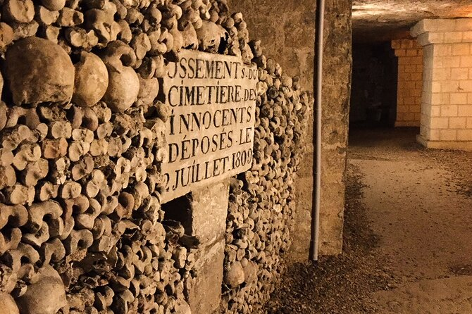 A wall of skulls within the catacombs with a stone plaque in the centre with a message in french in block capital letters upon it. dark tourism