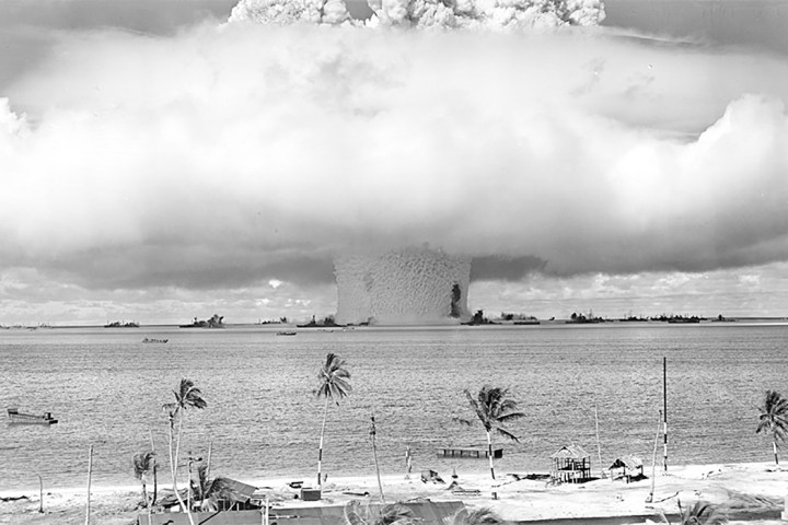 A black and white image of the coast of an island with an enormous mushroom cloud explosion occurring in the water just off the coast.