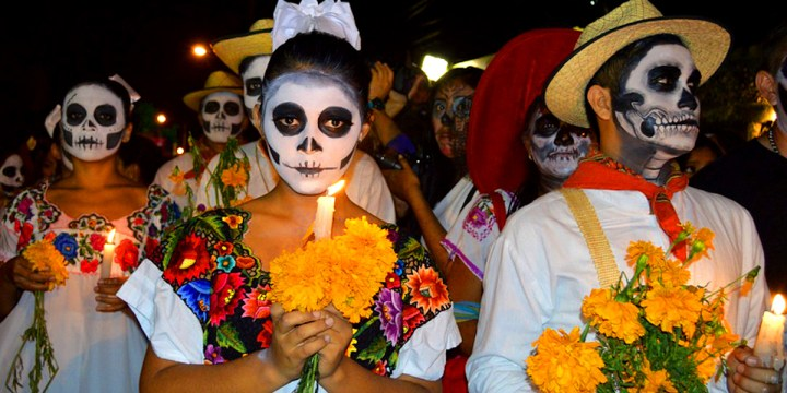 Three figures with skull face paint hold flowers and candles as they take part in a procession wearing traditional mexican costumes.