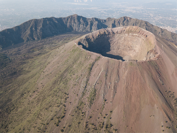 A photo of a large volcano with a huge circular crater on the top with rocky mountains and a blue sky in the background.