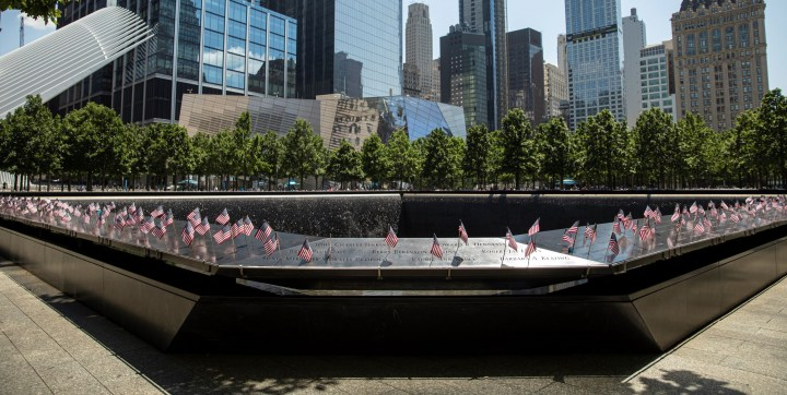 in front of a line of glass skyscraper buildings lies a silver monument covered in small american flags.