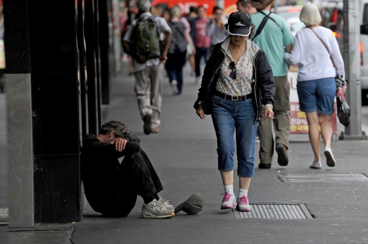 A man sits with his head in his knees against a busy side walk as people walk by