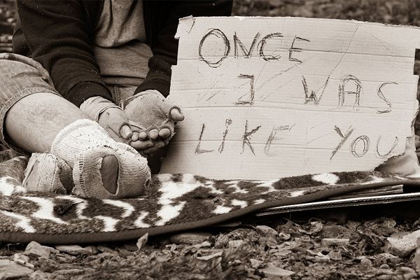 Sepia toned image of a homeless person's lower body with a sign beside them reading 'once I was like you'