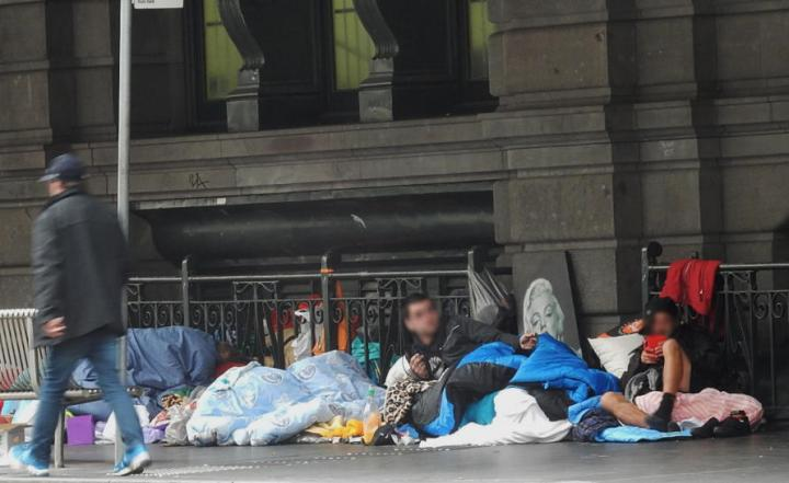 Five homeless people wrapped in sleeping bags sit on the conrete floor against a stone wall