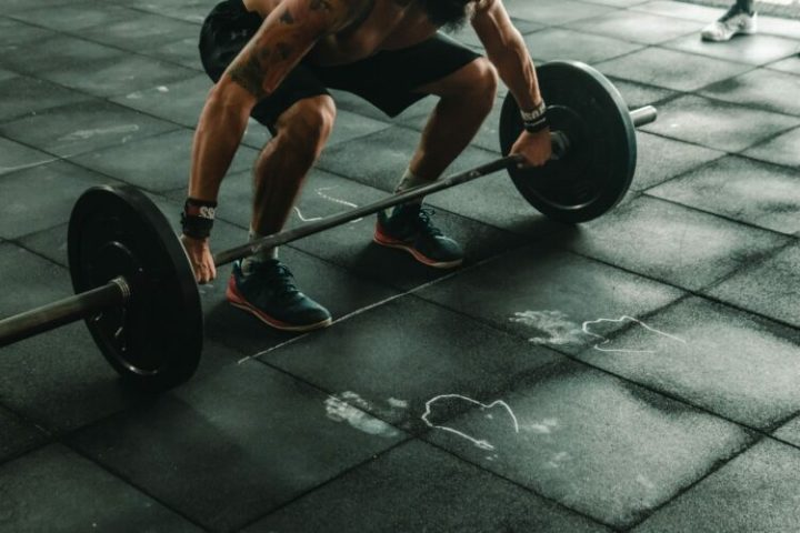 A person about to lift a long barbell.