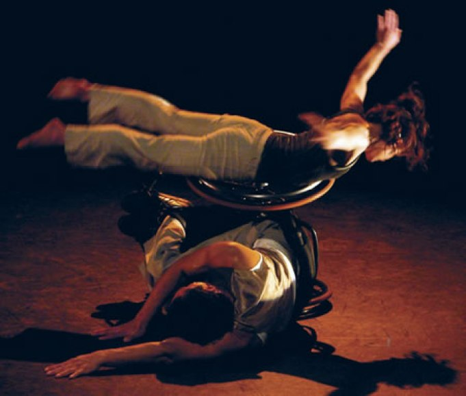 a colored image of dancers performing, as the one in the wheelchair lying on the floor and the other dancer lies on the tyre of the wheelchair, opening her arms