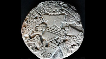 plae grey stone disk of Coyolxauhqui, a figure with her limbers dismembered with an aztec motif
