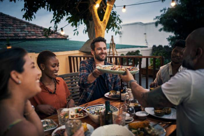 Shot of a group of young friends having a dinner party outdoors