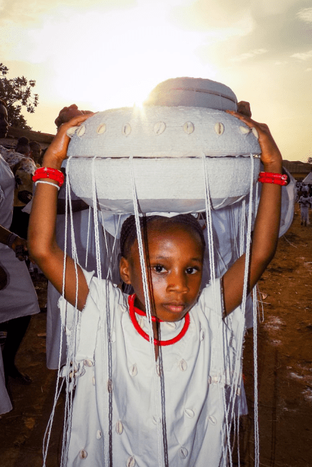 A Yoruba boy attending a Osun-Osogbo Festival. He is wearing ceremonial clothes and holds a big white artefact on top of his head.