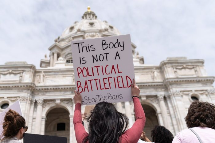 Woman holds up a sign 'this body in not a political battlefield' at a Stop Abortion Bans Rally in St Paul, Minnesota