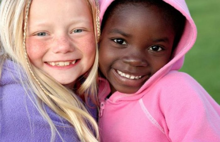 White and black kids smiling together in the garden