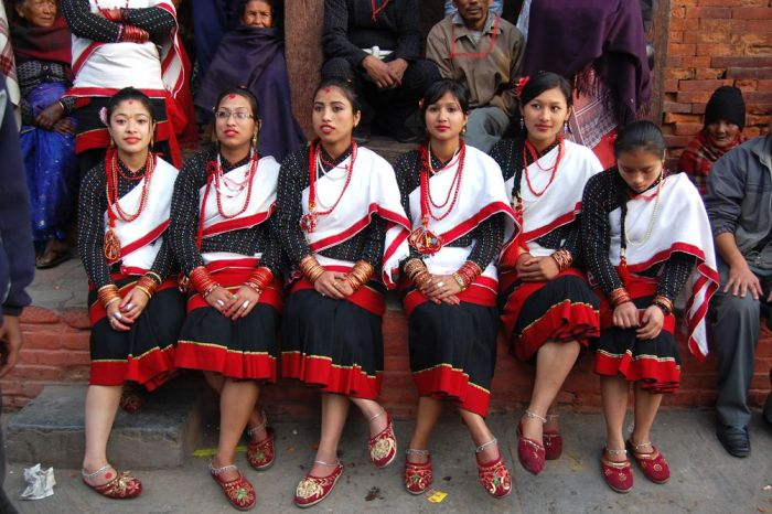 Six Newar girls posing for a photo in their traditional outfits and jewelry. The red shoes are also a part of their traditional Newari outfi