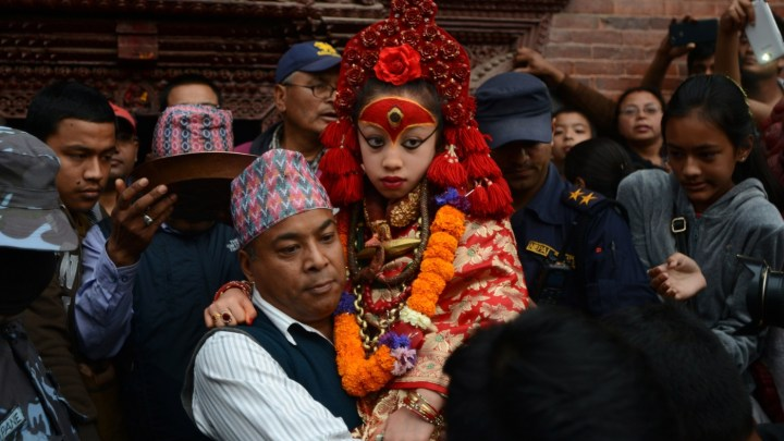 """Nepal's Living Goddess, the Kumari Devi, 9, observes a chariot festival in Kathmandu on March 29. Her caretaker, Gautam Shakya, carries her as she is not allowed to walk on the """" impure"""" floor. The people in the background seek her blessings as she passes by them."""