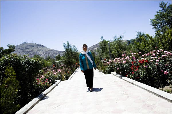 A woman walks down a stone path in the middle of a garden