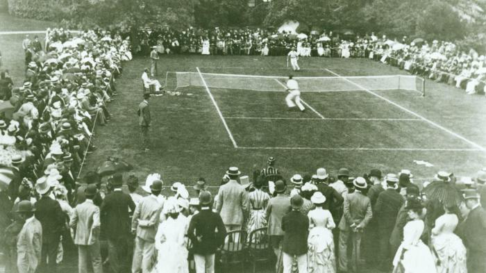 A black and white photo, most likely taken during the late 1800s, of the U.S. National Championship. The players are playing on a grass court, and they are surrounded by spectators.