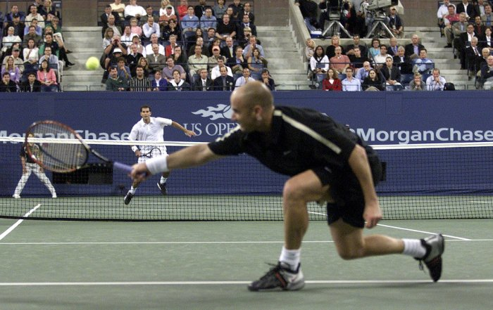 A courtside photo of Andre Agassi and Peter Sampras playing their 2001 quarterfinals match. Agassi is returning Sampras' shot with a backhand shot.