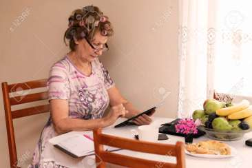 The photograph of an elderly lady calculating her budget at the kitchen table.