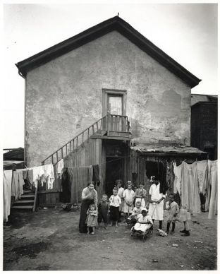 The photograph of an impoverished house and a family of 13 standing outside of it.