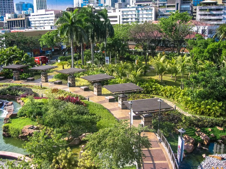 A pathway surrounded by shaded seating areas. To the left of the pathway is a pond, artfully scattered with lush grass, small trees, and other colourful decorative plants. On the far right of the image, a city skyline emerges.