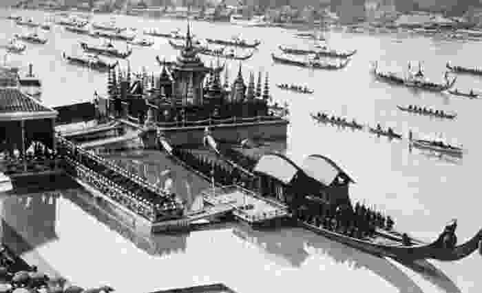 A black and white imag e of highly official boats making port or on the river as they make their way through a luxurious building built on the water.