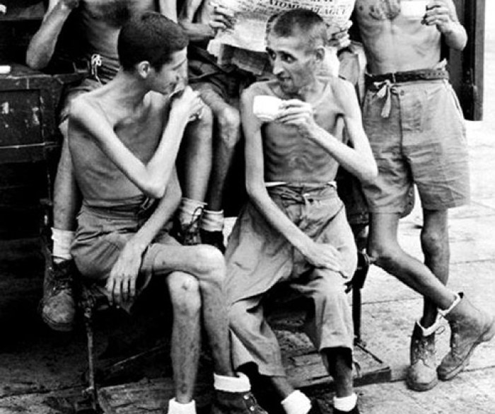 A black and white photograph of Australian POWs sipping cups of tea in Siam, talking with one another after discovering the war ended.
