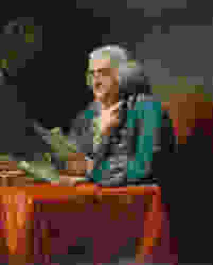 An illustration of a grey-haired man in spectacles reading a paper at a desk.