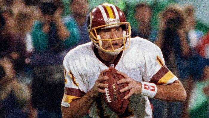 Mark Rypein in action during a game. He is holding on to a football.