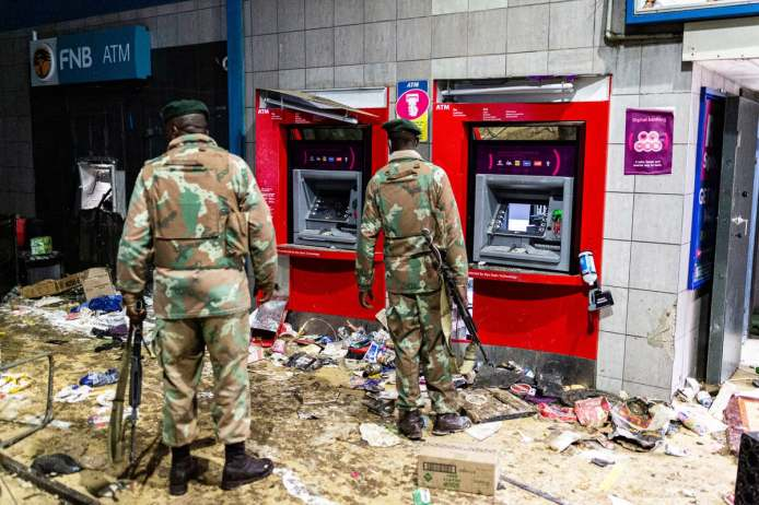 a colored image of two soldiers standing inside of a building in front of the ATMs that were looted