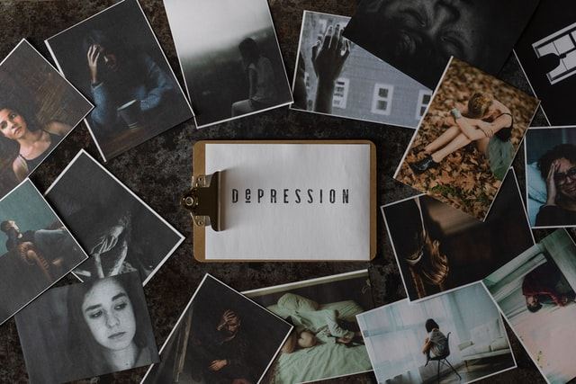 Many printed pictures surrounding a paper with the word depression written on it