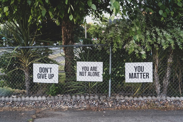 Three signs reading 'Don't give up', 'You're not alone', and 'You matter'
