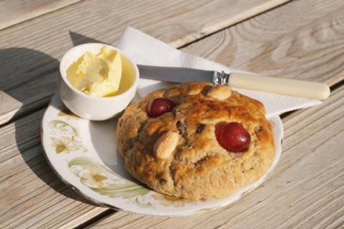 A photo of a rock cake with cherries and almonds on top on a plate