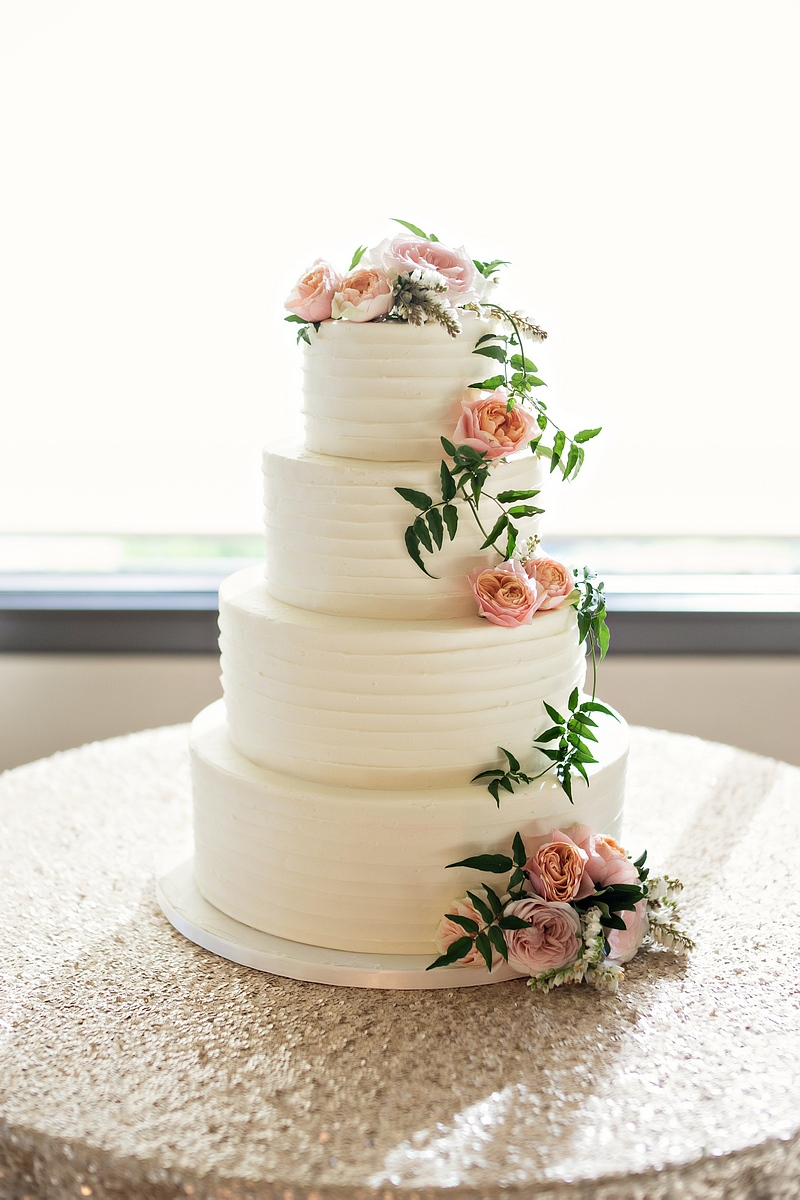 Wedding Cakes  Pros and Cons of Buttercream vs  Fondant   Inside     White buttercream frosting wedding cake with pink flowers and vines  cascading down