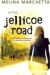 There's a girl's silhouet from the back and against the sunlight on the right side of the picture. She's almost transparent. On the left side there's a picture of a road and a group of three walking by it.  Author: Melina Marchetta. Title: On the Jellicoe Road.