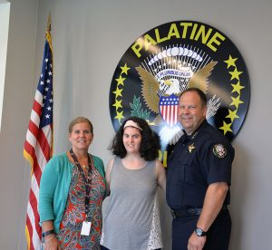 Allison (center) works at the Palatine Police Department. She poses with Palatine Police Chief Alan Stoeckel and his assistant Kathy Leffelyoung.