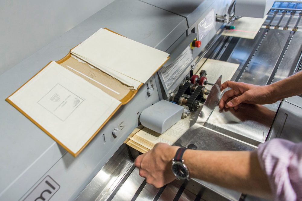 One of Harvard's case law books goes through the high speed scanner. (Brooks Kraft/Harvard Law School)