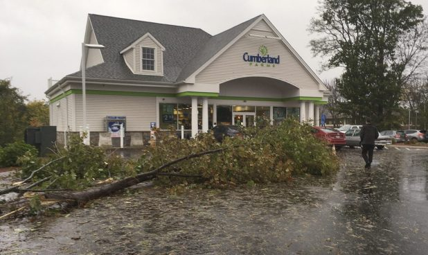 A toppled tree fills part of the parking lot at a Cumberland Farms after an overnight storm on Monday in Glastonbury, Conn. (Dave Collins/AP)
