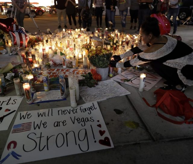 A Woman Places A Candle At A Memorial For Victims Of The Mass Shooting Tuesday