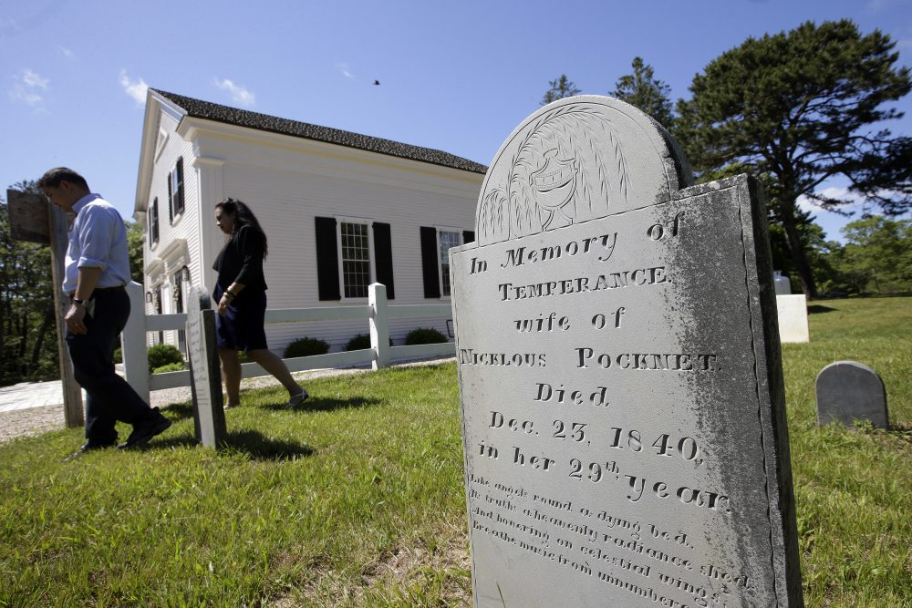 A gravestone dated 1840 stands near the Mashpee Old Indian Meeting House, behind, on Mashpee Wampanoag tribal land, on Cape Cod.  (Steven Senne/AP)