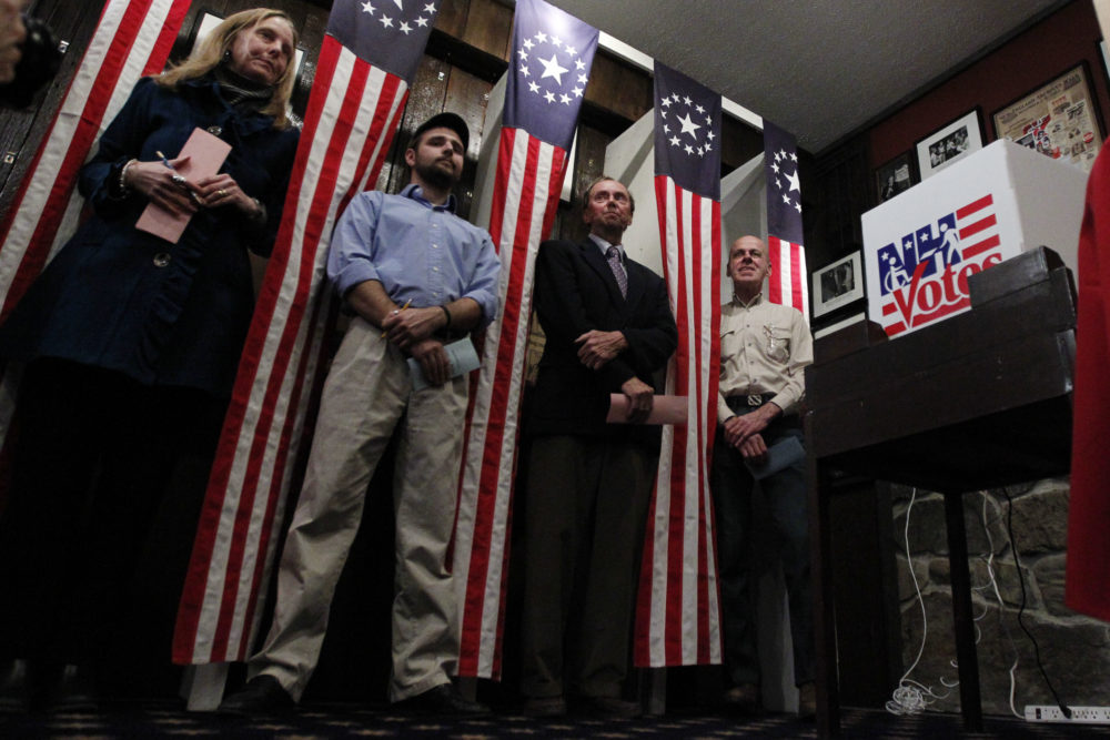 From left, Donna Kaye Erwin, Tanner Tillotson, Peter Johnson, and Jacques Couture wait for the stoke of midnight to cast their voters in the first-in-the-nation presidential primary at The Balsams Grand Resort in 2012. (Matt Rourke/AP)