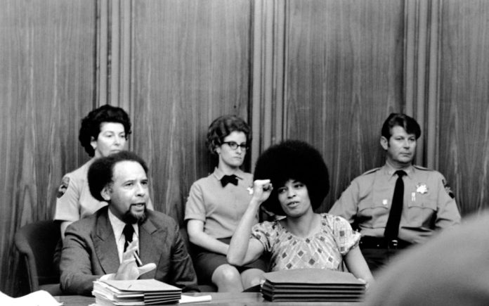 Angela Davis raises her fist to give her power salute as she sits in the courtroom at Marin Civic Center in San Rafael, Ca., on March 16, 1971. (AP Photo)