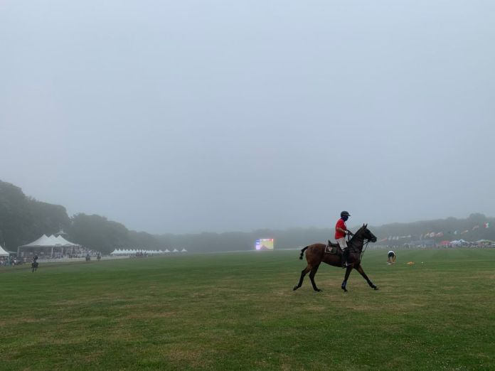 A player takes a final lap as fog covers the polo field at Glen Farm. (Antonia Ayres-Brown/The Public's Radio)