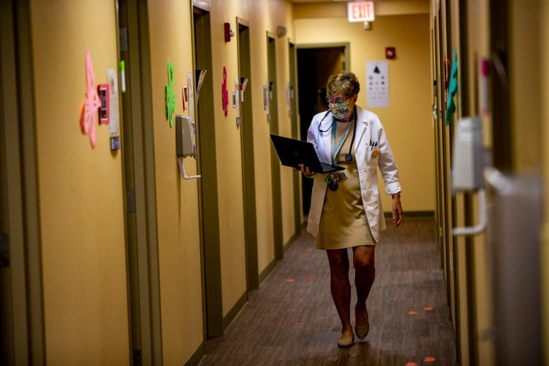 After finishing up an exam with a patient, pediatrician Dr. Janemarie Dolan walks through the corridor of Brockton Neighborhood Health Center to visit her next patient. (Jesse Costa/WBUR)