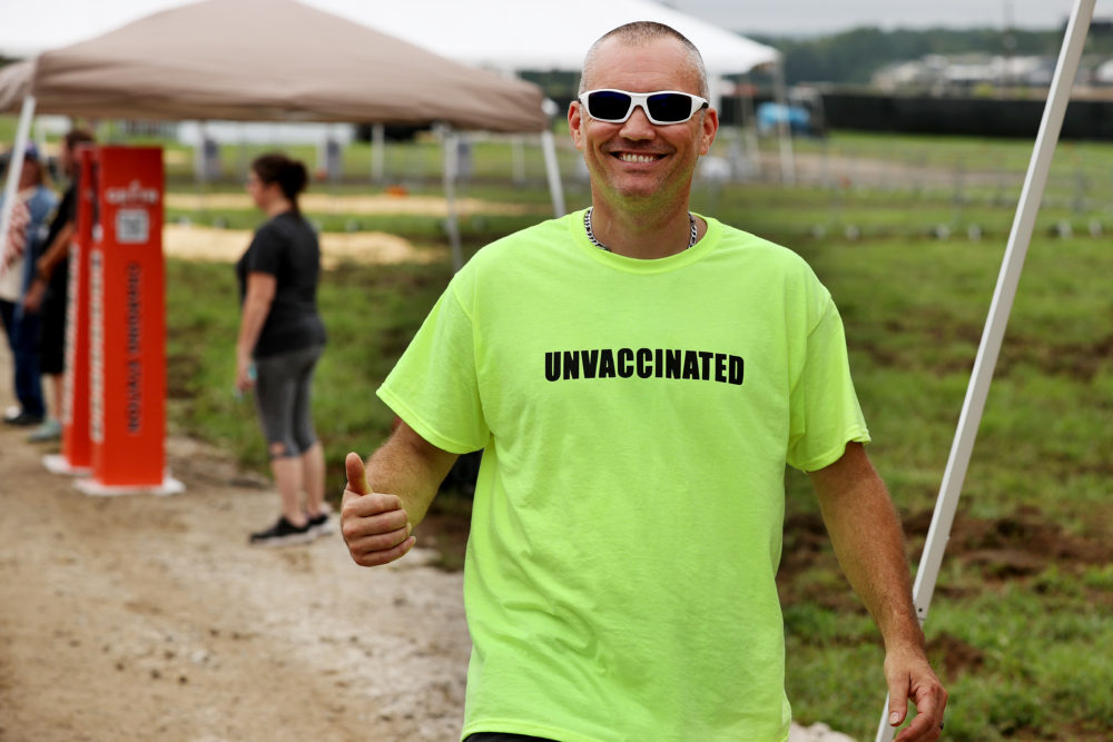 """A man wears an 'UNVACCINATED' t-shirt ahead of U.S. President Donald Trump's """"Save America"""" rally at York Family Farms on August 21, 2021 in Cullman, Alabama. With the number of coronavirus cases rising rapidly and no more ICU beds available in Alabama, the host city of Cullman declared a COVID-19-related state of emergency two days before the Trump rally. According to the Alabama Department of Public Health, 67.5% of the state's population has not been fully vaccinated. (Chip Somodevilla/Getty Images)"""